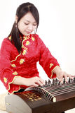 Young musician. Chinese zither performer in traditional dress playing zither on white Royalty Free Stock Images