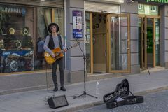 Young musician boy playing guitar and singing songs on street Stock Photo