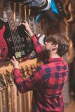 Young musician choosing a bass guitar. In a music store stock images