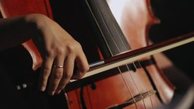 Young musician girl playing with cello violoncello in symphonic hall. In slow motion stock footage