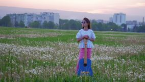 Young musician girl on sunglasses stands in the field with a blue guitar in the evening in background cityscape. concept of inspir. Young musician girl on
