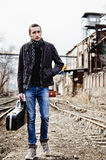 Young musician with guitar case among ruins Royalty Free Stock Images