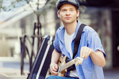 Young musician with guitar in city Royalty Free Stock Photos