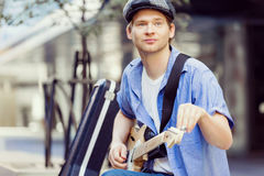 Young musician with guitar in city Royalty Free Stock Photography