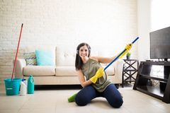 Girl with headphones and a broom stock photography