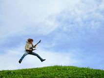 Young musician jumps with guitar. On meadow under clear sky Stock Photography