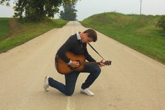 Young musician on knee. Playing classic guitar on asphalt road royalty free stock photography