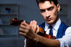 The young musician man practicing playing violin at home. Young musician man practicing playing violin at home Stock Photography