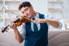 The young musician man practicing playing violin at home. Young musician man practicing playing violin at home Stock Photo
