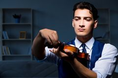 The young musician man practicing playing violin at home Royalty Free Stock Photo