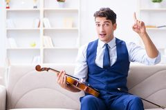 The young musician man practicing playing violin at home Stock Image
