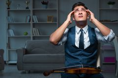 The young musician man practicing playing violin at home Stock Images
