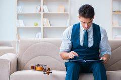 The young musician man practicing playing violin at home Royalty Free Stock Image