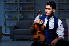 The young musician man practicing playing violin at home Stock Photos