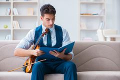The young musician man practicing playing violin at home. Young musician man practicing playing violin at home Royalty Free Stock Photography