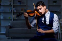 The young musician man practicing playing violin at home. Young musician man practicing playing violin at home Royalty Free Stock Images