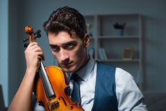 The young musician man practicing playing violin at home. Young musician man practicing playing violin at home Stock Images