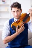 The young musician man practicing playing violin at home. Young musician man practicing playing violin at home Royalty Free Stock Photos