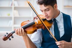 The young musician man practicing playing violin at home. Young musician man practicing playing violin at home Stock Image