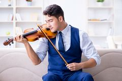 The young musician man practicing playing violin at home. Young musician man practicing playing violin at home Royalty Free Stock Image