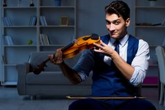 The young musician man practicing playing violin at home. Young musician man practicing playing violin at home Royalty Free Stock Photo