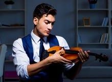 Young musician man practicing playing violin at home royalty free stock photos