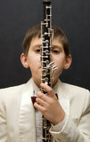 Young musician with oboe. Portrait of the young musician on a dark background Stock Image