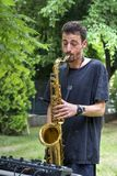 Young musician performing street music on saxophone. Playing for arts festival Stock Photos
