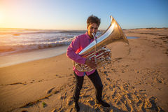 Young musician play the trumpet on rocky sea coast during surf. Tuba instrument Royalty Free Stock Photography
