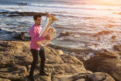 Young musician play the Tuba on rocky sea coast during surf. Trumpet Stock Image