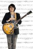 Young musician playing guitar. Asian young musician playing guitar on note background Royalty Free Stock Images