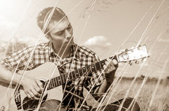 Young musician playing guitar in nature Royalty Free Stock Photos