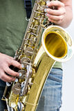 Young musician playing jazz on street. Men playing brass alto saxophone during a live performance Stock Photos