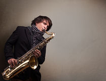 Young musician playing on saxophone Stock Image
