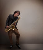 Young musician playing on saxophone Stock Photos