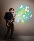 Young musician playing on saxophone while musical notes explodin Royalty Free Stock Photography