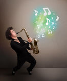 Young musician playing on saxophone while musical notes explodin Stock Photos
