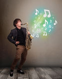 Young musician playing on saxophone while musical notes explodin Stock Photo