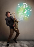 Young musician playing on saxophone while musical notes explodin Stock Image