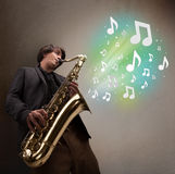 Young musician playing on saxophone while musical notes explodin Stock Images
