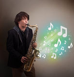 Young musician playing on saxophone while musical notes explodin Royalty Free Stock Images