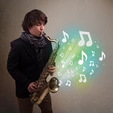 Young musician playing on saxophone while musical notes explodin Royalty Free Stock Photos