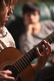 Young Musician Plays His Guitar as Friend Listens Royalty Free Stock Photo