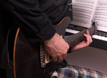 Young musician practicing. Young musician with an electric guitar, keyboards and notes, practicing a musical piece Royalty Free Stock Photography
