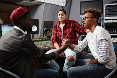 Collaboration. Young musician and sound operator making agreement about cooperation in audio studio stock image