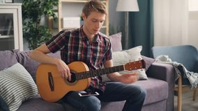 Young musician is tuning acoustic guitar touching strings sitting on couch at home during leisure time. Youth lifestyle. Young male musician is tuning acoustic stock footage