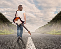 Young musician woman walking on a road Royalty Free Stock Photography
