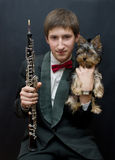 Young musician with Yorkshire dog. Portrait of the young musician on a dark background Stock Photos
