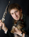 Young musician with Yorkshire dog. Portrait of the young musician on a dark background Stock Photo