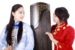 Young musicians. Two Chinese musicians with bamboo flute and zither talking on white Royalty Free Stock Photography
